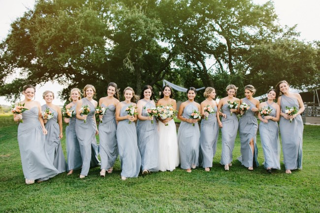 Bride with 13 bridesmaids wearing floor length gray gowns
