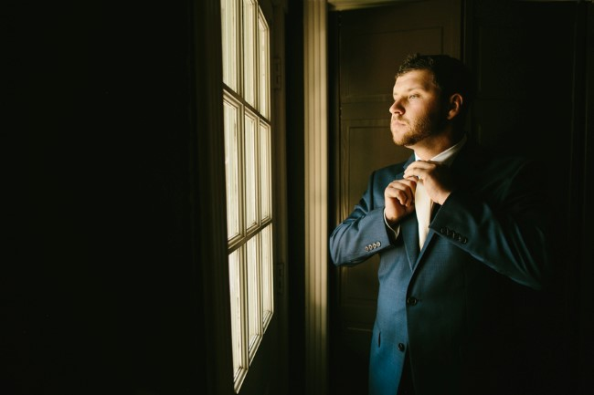 Groom wearing dark blue suit and yellow tie captured by Brant Smith Photography
