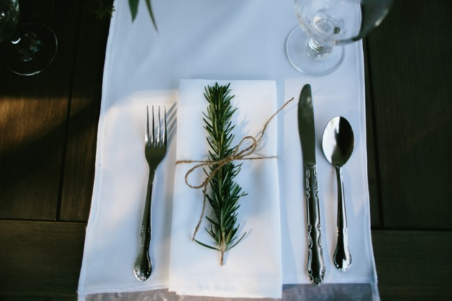 table setting with white cloth and rosemary for wedding at Stonehouse Villa