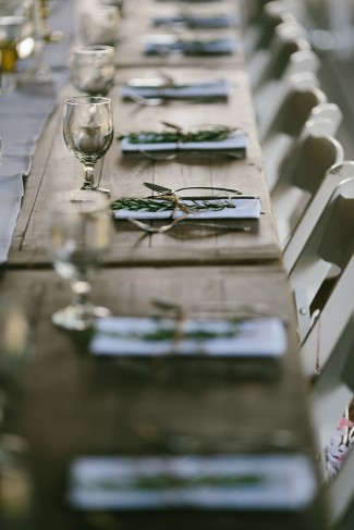 Basic wedding reception place setting with white napkin and a pieces of rosemary
