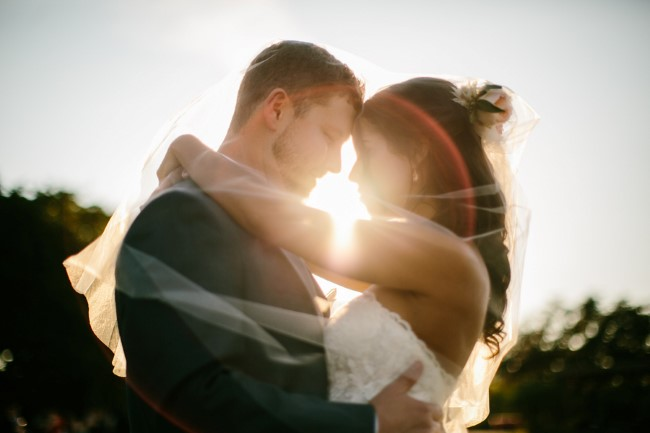 Bride and groom head to head with sun shinning through captured by Brant Smith Photography