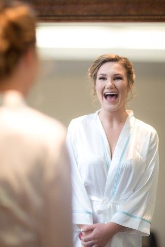 bride looking at herself in the mirror with a big smile wearing a white silk robe