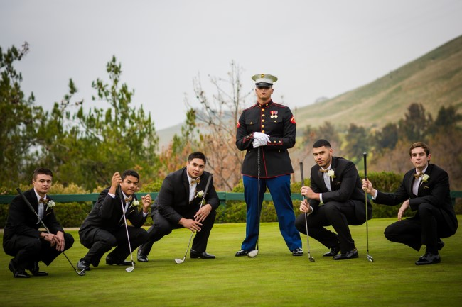 Groom wearing military suit surrounded by groomsmen wearing black tuxedos