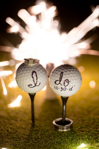2 golf balls with I do written on them and a sparkler behind