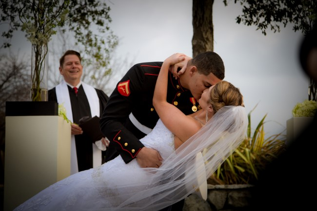 Groom kissing bride during outdoor wedding at Oakhurst Country Club