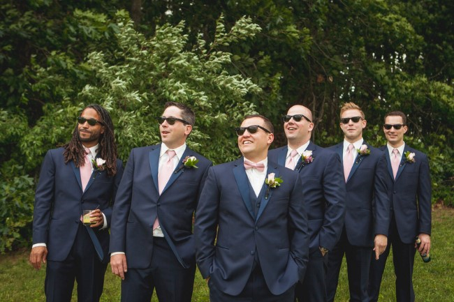 Groomsmen wearing sun glasses, navy blue suits and pink ties