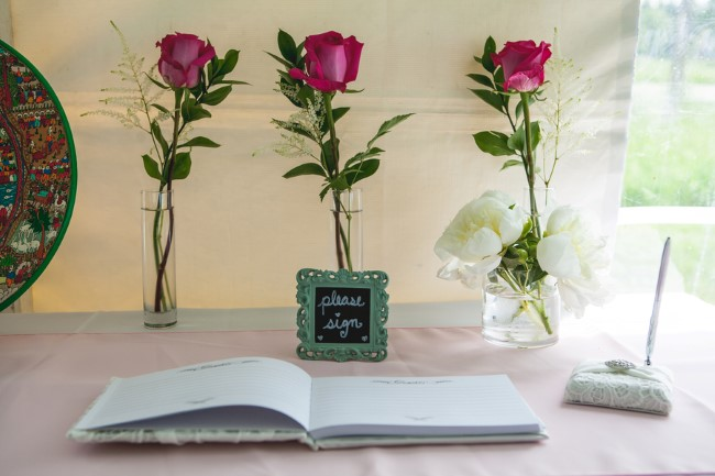 Wedding guest book in front of three pink roses