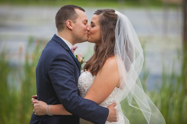 Bride wearing a veil kissing her groom during outdoor backyard wedding ceremony