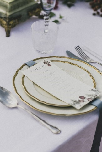 White china with gold rim and menu and silver ribbon in the center designed by Coquette Atelier