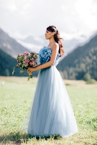 Bride wearing blue gown holding pink flowers with green foliage created byLe jardin d'Amelie