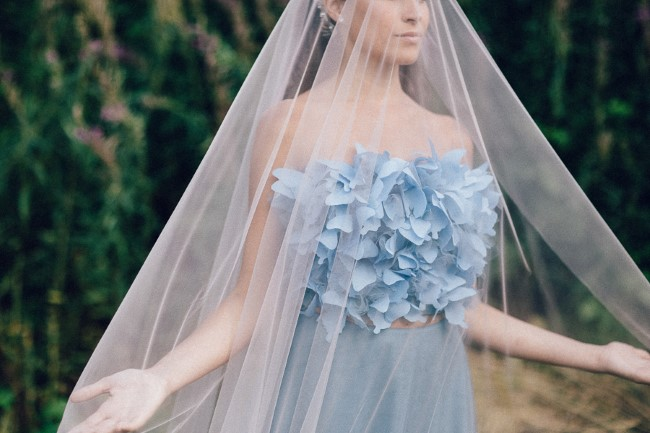 Bride wearing blue gown from Il Sogno Atelier and chapel length drop veil holding her hands out