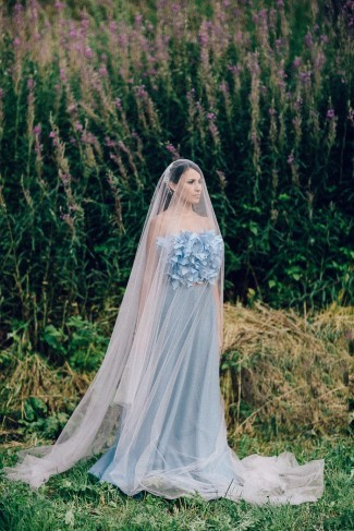 Bride wearing drop chapel length veil and blue gown