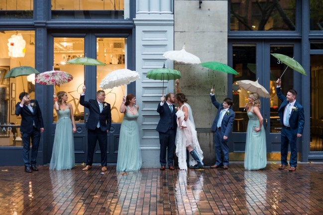 Bride and groom with wedding party in Seattle holding green umbrellas captured by Lindsay Murphy Photography