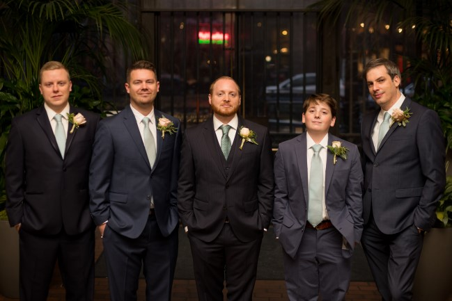 Groom with groomsmen in black, and blue suits and green ties