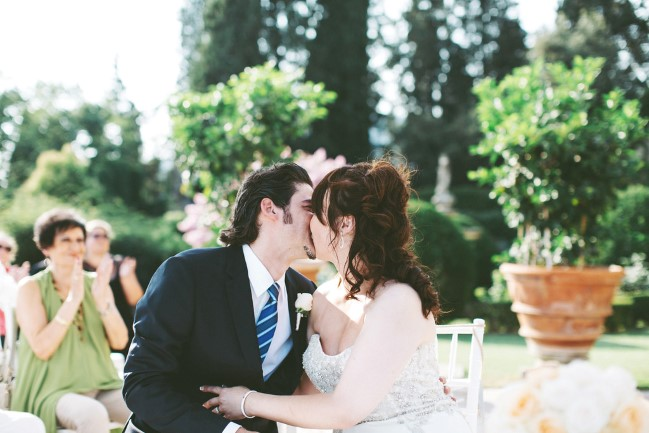 Bride and groom kissing during outdoor wedding ceremony at Castello di Vincigliata, Fiesole, Italy