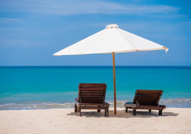 sand beach with two chairs and umbrella
