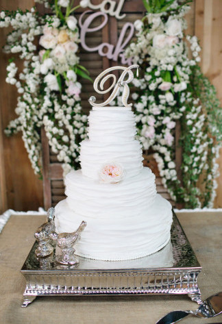 white wedding cake on square silver stand with two metal lovebird figurines