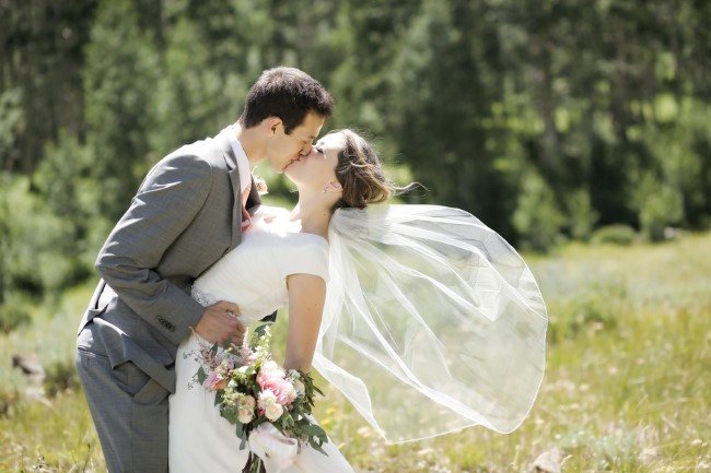 newlyweds kiss in the sunshine with veil blowing in wind