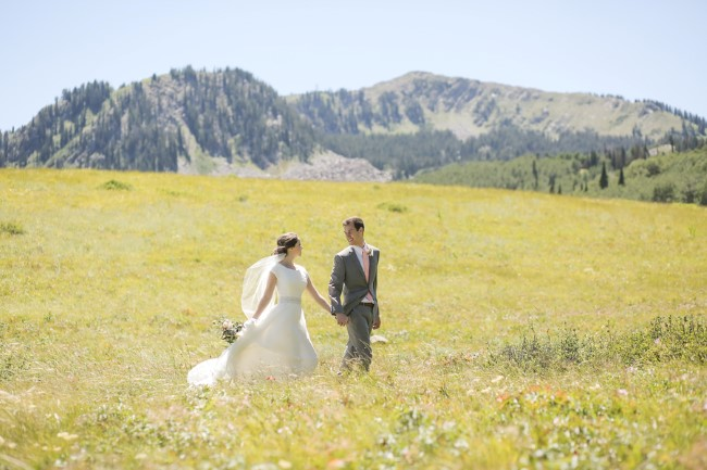 newlyweds walk in open field with mountain backdrop