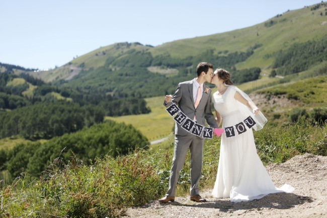 "Newlyweds hold ""Thank You"" sign standing outside with mountains behind"