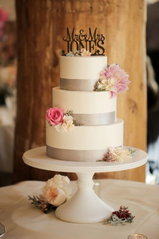 white cake on white platter with Mr & Mrs Jones cake topper