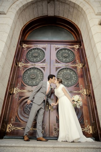 newlyweds kiss in front of large wood doors