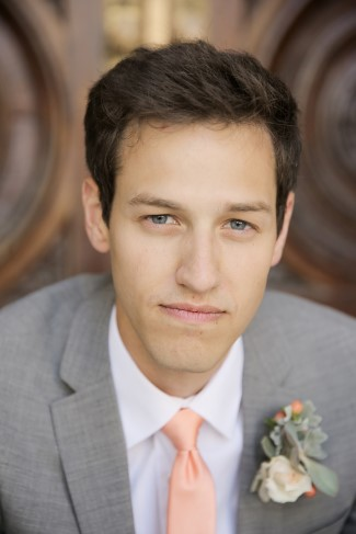 young groom in salmon pink necktie with grey suit