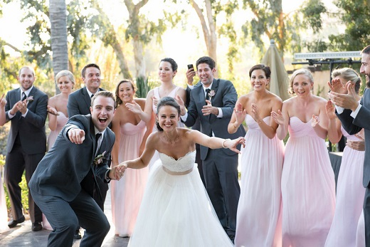 Bride and groom goofing off outside with bridal party