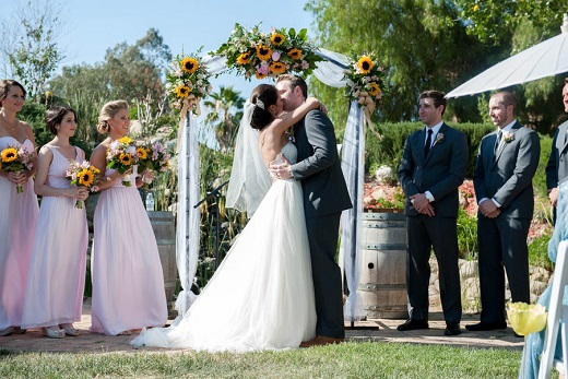 Bride and groom kissing during outdoor ceremony at Bella Gardens Estates