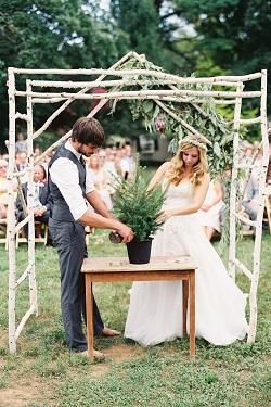 Bride and groom planting a tree during a rustic outdoor wedding ceremony