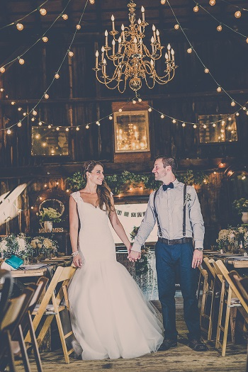 Bride and groom standing in rustic themed barn with gold chandalier at Jack's Barn