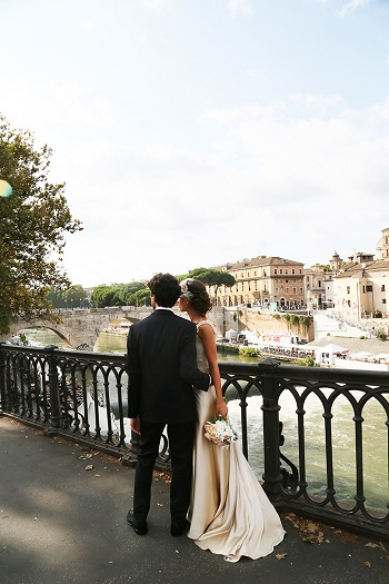 Bride and groom standing together near a river in Italy captured by Avorio photo