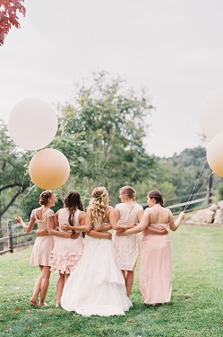 Bride standing with bridesmaid holding geronimo balloons