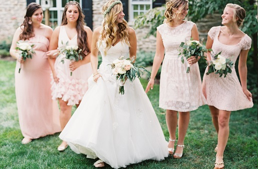 Bride wearing a baby's breath flower crown posing with bridemaids in pink dresses from Modcloth