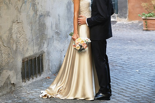 Bride wearing a silk dress standing with groom in the streets of italy