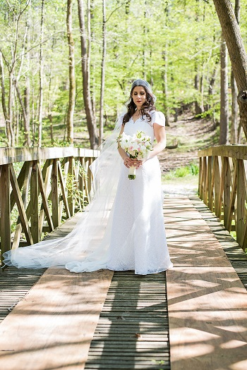 Bride wearing downton abbey inspired bridal outfit standing on bridge