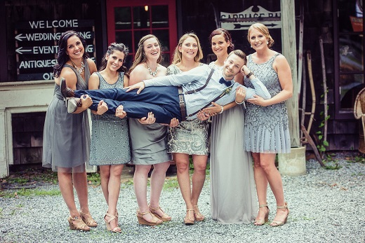 Bridesmaids in grey holding up groom wearing suspenders and a bow tie
