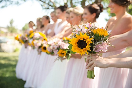 Bridesmaids wearing pink dresses from nordstrom holding sun flower bouquets