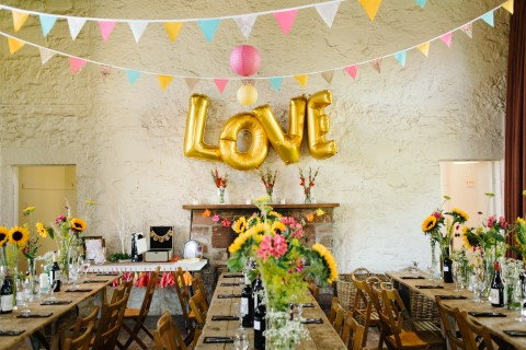 Colorful wedding with bunting and gold foil balloons spelling LOVE