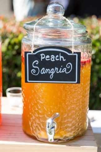 "glass drink dispenser with ""peach sangria"" sign"