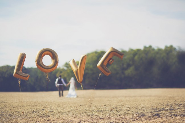 Gold Balloon Bride and groom standing in a field