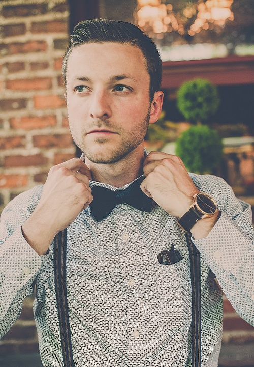 Groom getting ready wearing black bow tie and suspenders