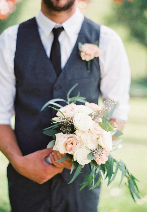 Groom wearing grey vest and black tie wearing a pink carnation boutonniere