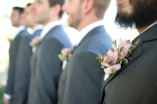 Groom with groomsmen wearing grey suits and pink boutonnieres