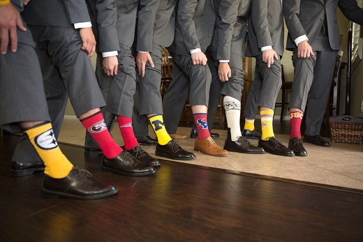 Groomsmen wearing sport socks and lifting their pants up to show them off