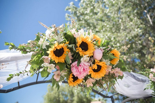 Outdoor wedding ceremony alter with sunflowers at Bella Gardens Estates