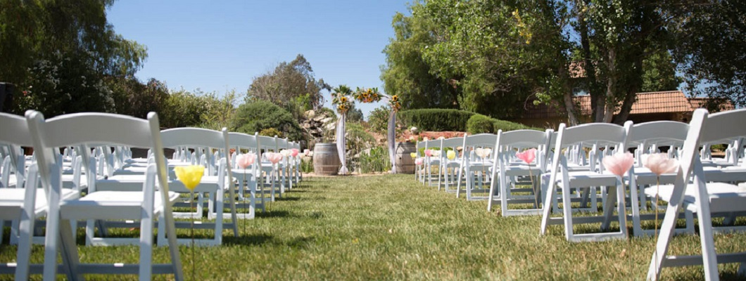 Outdoor wedding ceremony with white folding chairs at Bella Gardens Estates