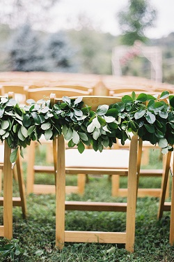 Outdoor wedding ceremony with wood chairs and green foliage hanging from them