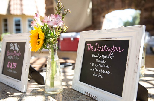 Outdoor wedding reception bar menu using white frames and chalkboard