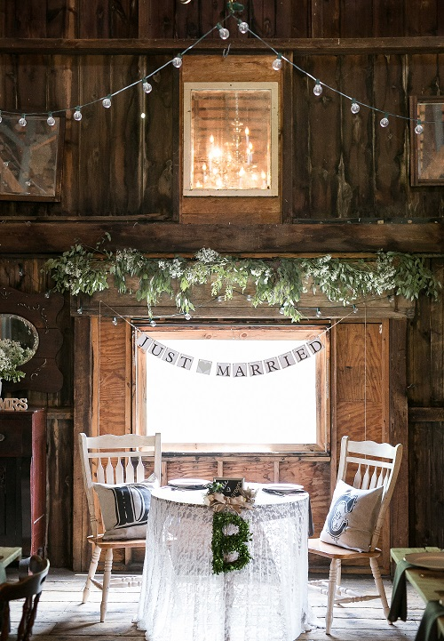 Rustic bride and groom sweetheart table with lace table cloth